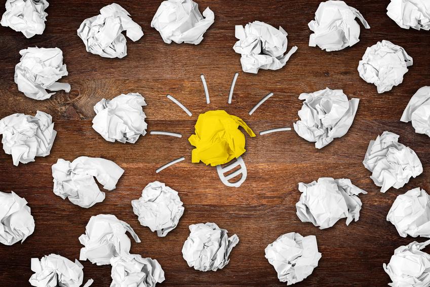 wooden desktop with many paper balls and lightbulb idea symbol / holz schreibtisch mit Papierknuel und Glhbirne Idee Symbol