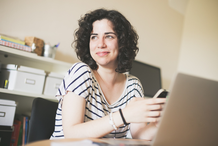 Young woman using her phone at her workplace.