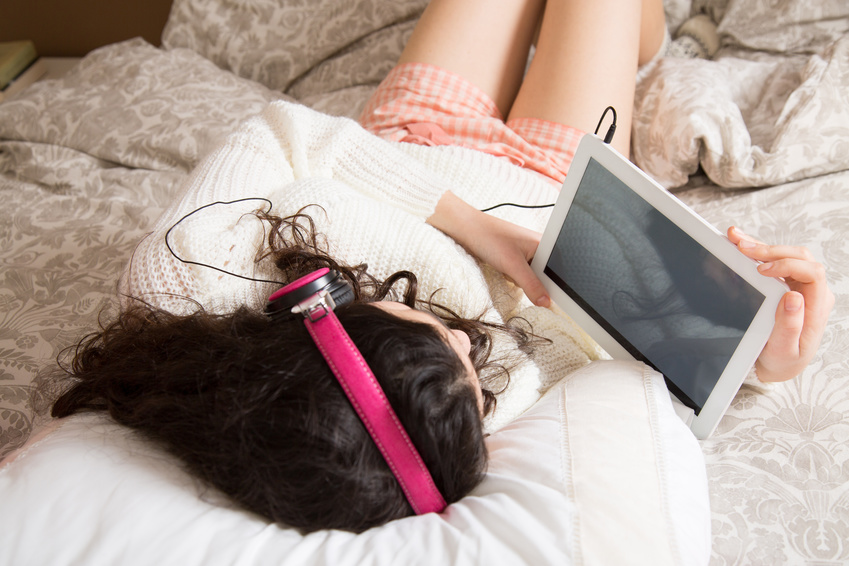 Girl with headphones watching something  in her tablet lying in bed