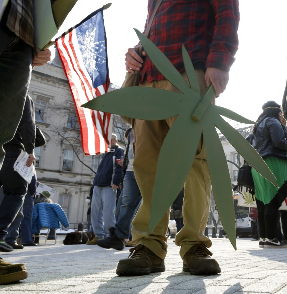 People hold flags and signs with marijuana depictions as a large group gathered near the New Jersey Statehouse to show their support for legalizing marijuana Saturday, March 21, 2015, in Trenton, N.J.The event drew a diverse crowd of roughly 200 people. Many said they wanted to show their support for legalizing or decriminalizing pot, while others said it should only be given to people with medical conditions that could be eased by the drug. Several people were openly smoking the drug during Saturday's rally, but apparently none were arrested. (AP Photo/Mel Evans)